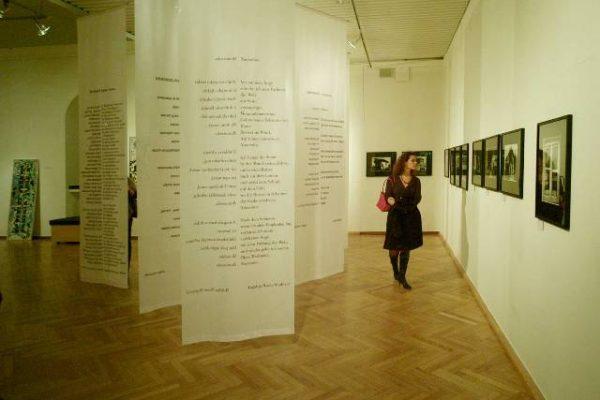 Die Gedichte der Kölner Roma-Autoren Jovan Nikolić, Ruždija Sejdović und Papusza Wajs (Polen) auf Fahnen. An der Wand Fotografien von Judit M. Horvath und György Stalter (beide Budapest)